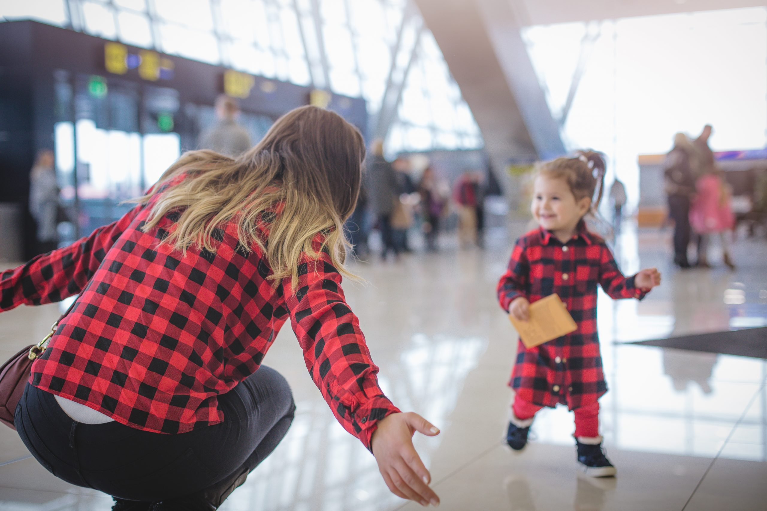 Mom is welcoming her baby girl with arms outstretched and matching clothes at station.